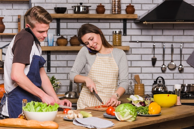 Jeune couple, préparer, salade, pendant, conversation smartphone