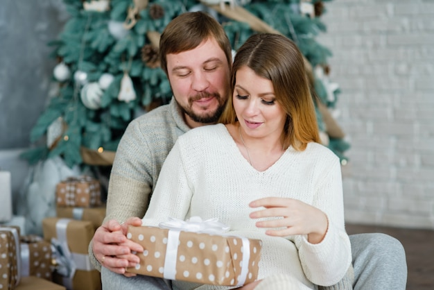 Jeune couple près de l'arbre de noël. femme avec mari. homme étreignant la fille. boîte de cadeau de nouvel an.
