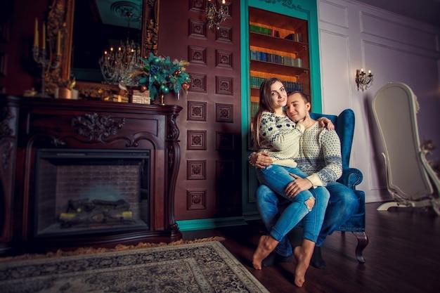 Jeune couple près de la cheminée à la maison
