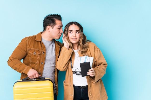 Jeune couple prêt pour un voyage isolé en essayant d'écouter un potin.