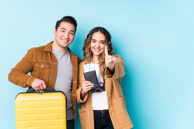 Jeune couple prêt pour un voyage isolé montrant le numéro un avec le doigt.