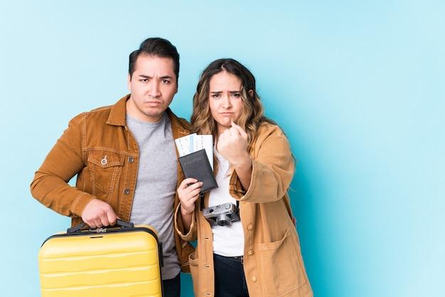 Jeune couple prêt pour un voyage isolé montrant le poing avec une expression faciale agressive.