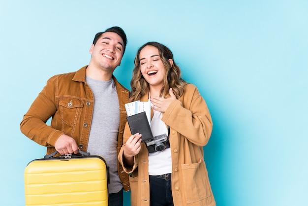 Jeune couple prêt pour un voyage isolé rit à haute voix en gardant la main sur la poitrine.