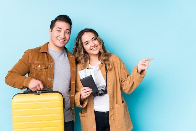Jeune couple prêt pour un voyage isolé souriant et pointant de côté, montrant quelque chose à l'espace vide.