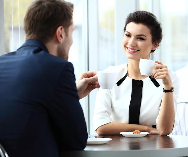 Jeune couple de professionnels discutant pendant une pause-café