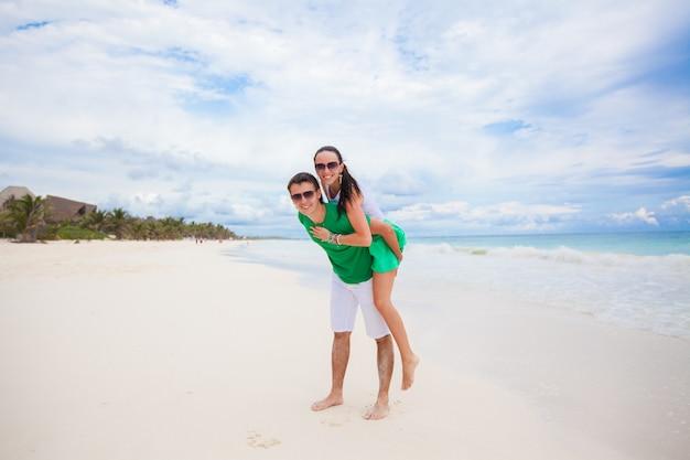 Jeune couple profitant de ses vacances et s'amusant sur une plage tropicale