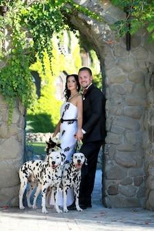 Un jeune couple promène un chien.