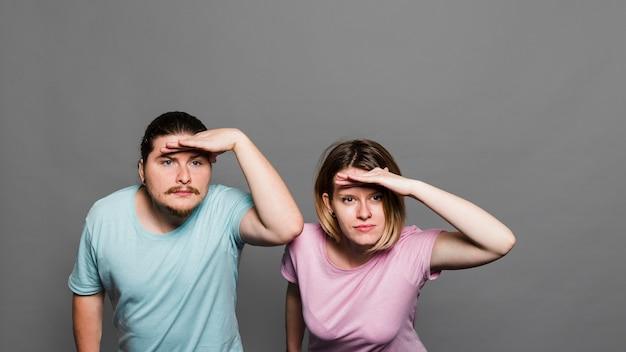 Jeune couple protégeant les yeux avec ses mains sur fond gris