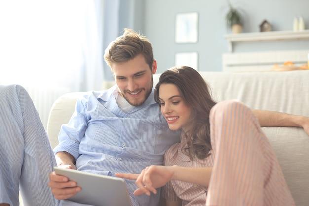 Jeune couple en pyjama regardant du contenu multimédia en ligne sur une tablette assise par terre dans le salon.