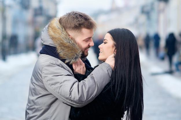Jeune couple de race blanche heureux et heureux s'embrasser tout en se promenant dans la rue en hiver sous la neige