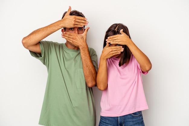 Jeune couple de race mixte isolé sur fond blanc clignote à la caméra à travers les doigts, gêné couvrant le visage.