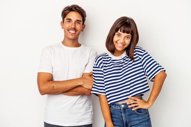 Jeune couple de race mixte isolé sur fond blanc confiant en gardant les mains sur les hanches.