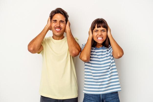 Jeune couple de race mixte isolé sur fond blanc couvrant les oreilles avec les mains.