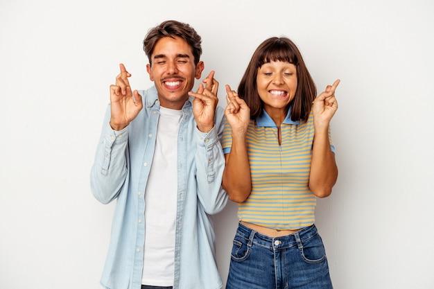 Jeune couple de race mixte isolé sur fond blanc croisant les doigts pour avoir de la chance