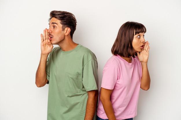 Un jeune couple de race mixte isolé sur fond blanc dit une nouvelle secrète de freinage à chaud et regarde de côté