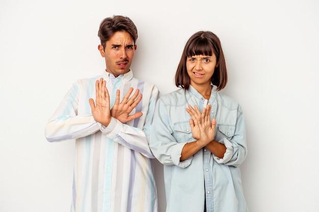 Jeune couple de race mixte isolé sur fond blanc faisant un geste de déni
