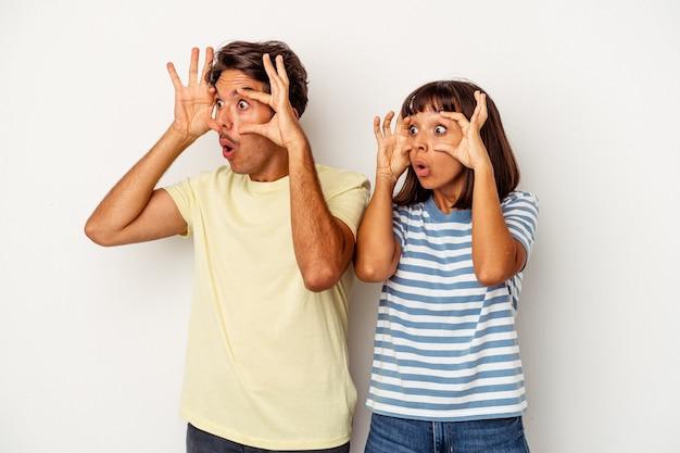 Jeune couple de race mixte isolé sur fond blanc en gardant les yeux ouverts pour trouver une opportunité de réussite.