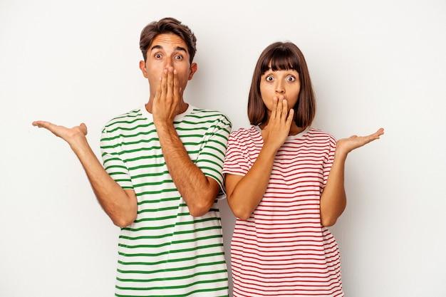 Jeune couple de race mixte isolé sur fond blanc impressionné tenant l'espace de copie sur la paume.