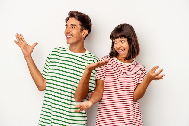 Jeune couple de race mixte isolé sur fond blanc joyeux rire beaucoup. notion de bonheur.