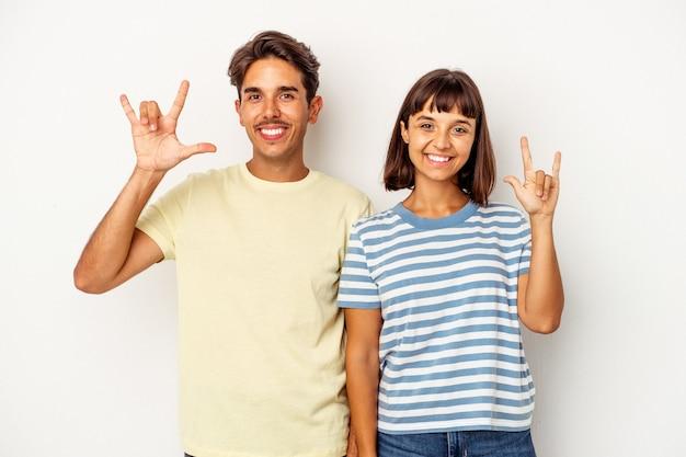 Jeune couple de race mixte isolé sur fond blanc montrant un geste de cornes comme concept de révolution.