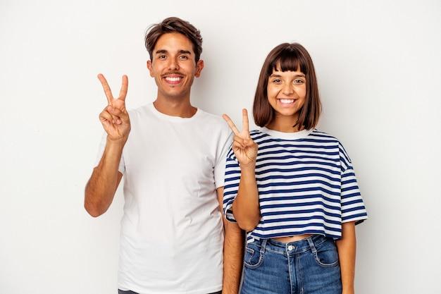 Jeune couple de race mixte isolé sur fond blanc montrant le numéro deux avec les doigts.