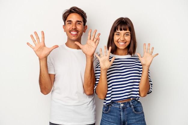 Jeune couple de race mixte isolé sur fond blanc montrant le numéro dix avec les mains.