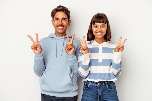 Jeune couple de race mixte isolé sur fond blanc montrant le signe de la victoire et souriant largement.