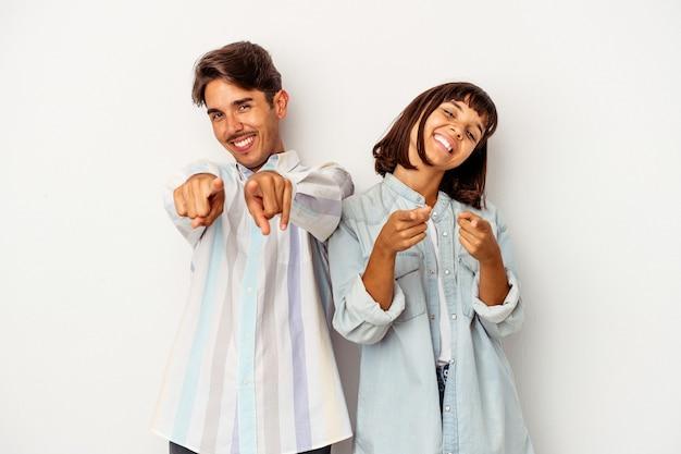 Jeune couple de race mixte isolé sur fond blanc pointant vers l'avant avec les doigts.