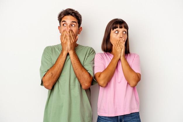 Jeune couple de race mixte isolé sur fond blanc réfléchi à la recherche d'un espace de copie couvrant la bouche avec la main.