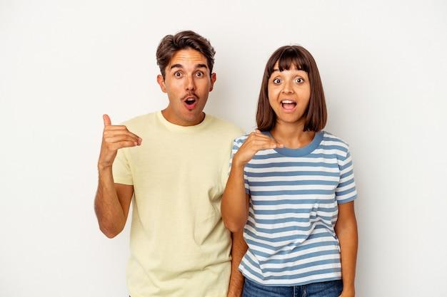 Jeune couple de race mixte isolé sur fond blanc en riant de quelque chose, couvrant la bouche avec les mains.