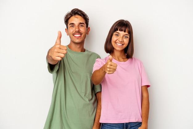 Jeune couple de race mixte isolé sur fond blanc souriant et levant le pouce vers le haut