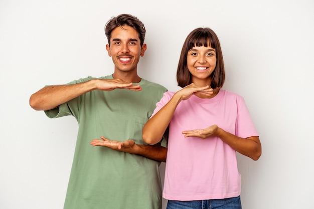 Jeune couple de race mixte isolé sur fond blanc tenant quelque chose avec les deux mains, présentation du produit.