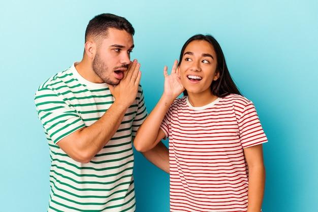Jeune couple de race mixte isolé sur fond bleu essayant d'écouter un potin.