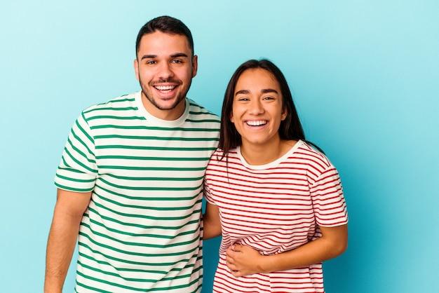 Jeune couple de race mixte isolé sur fond bleu en riant et en s'amusant.