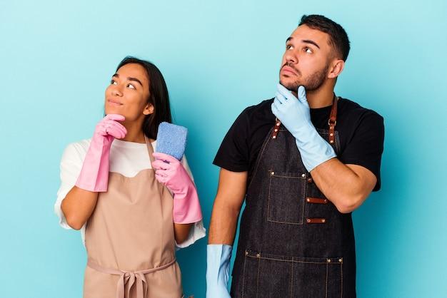 Jeune couple de race mixte nettoyant la maison isolée sur le bleu regardant de côté avec une expression douteuse et sceptique.