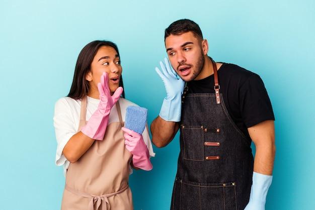 Jeune couple de race mixte nettoyant la maison isolée sur fond bleu dit une nouvelle secrète de freinage à chaud et regarde de côté