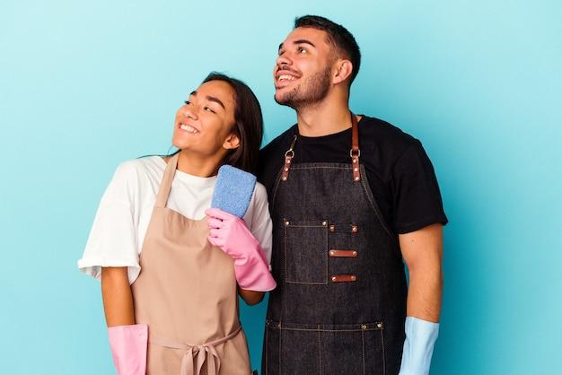 Jeune couple de race mixte nettoyant la maison isolée sur fond bleu rêvant d'atteindre des objectifs et des buts