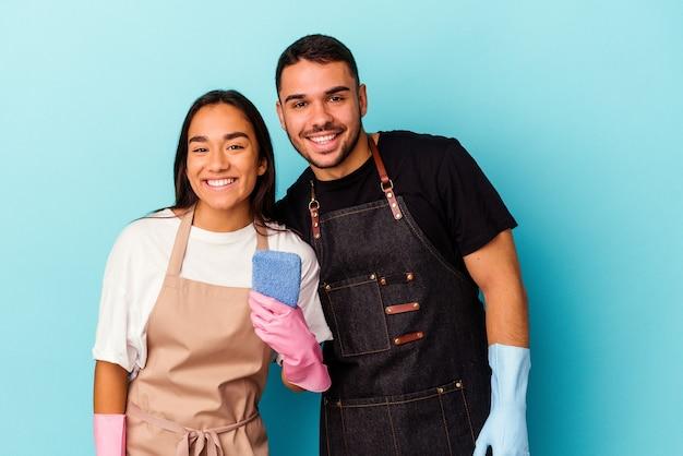 Jeune couple de race mixte nettoyant la maison isolée sur fond bleu en riant et en s'amusant.