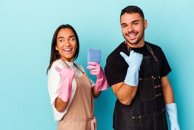 Jeune couple de race mixte nettoyant la maison isolée sur les points de fond bleu avec le pouce, riant et insouciant.