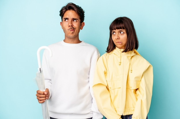 Jeune couple de race mixte tenant un parapluie isolé sur fond bleu confus, se sent douteux et incertain.