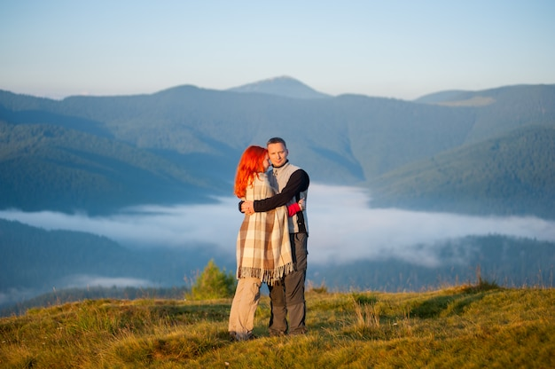 Jeune couple de randonneurs debout sur une colline, s'embrassant dans un magnifique paysage de montagne avec la brume matinale sur les montagnes à l'arrière-plan. femme rousse couverte d'un plaid