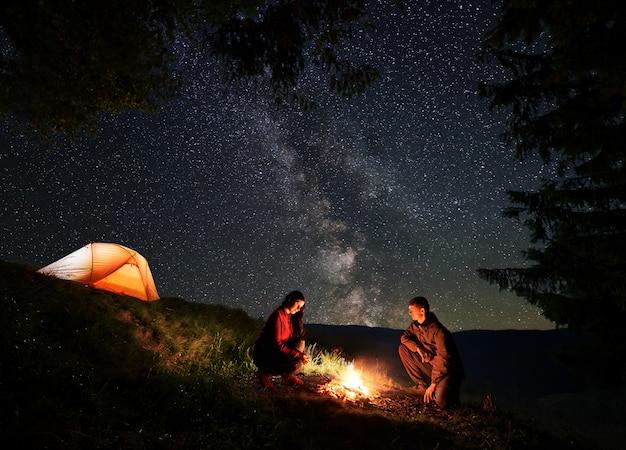 Jeune couple de randonneurs - hommes et femmes se chauffant autour du feu de camp la nuit