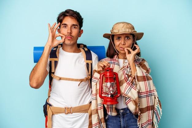 Jeune couple de randonneurs métis isolé sur fond bleu avec les doigts sur les lèvres gardant un secret.