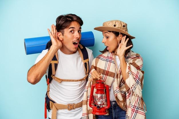 Jeune couple de randonneurs métis isolé sur fond bleu essayant d'écouter un potin.