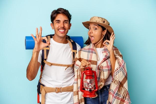 Jeune couple de randonneurs métis isolé sur fond bleu joyeux et confiant montrant un geste correct.