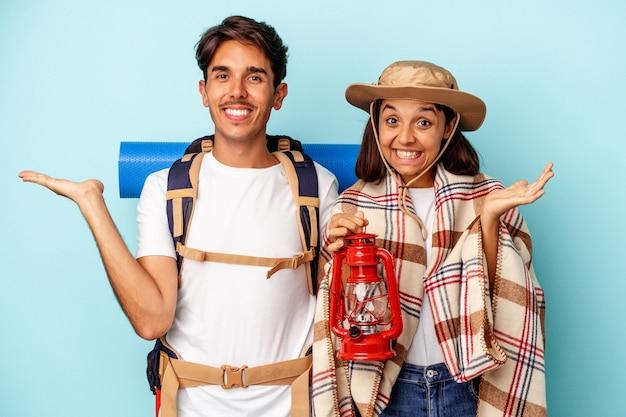 Jeune couple de randonneurs métis isolé sur fond bleu montrant un espace de copie sur une paume et tenant une autre main sur la taille.