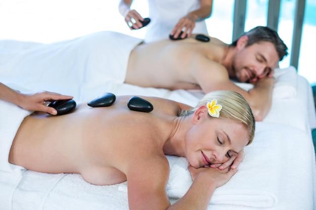 Jeune couple recevant un massage aux pierres chaudes d'un masseur