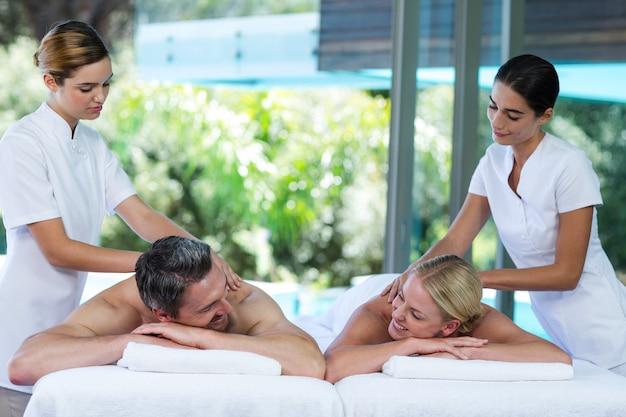 Jeune couple recevant un massage du dos d'un masseur