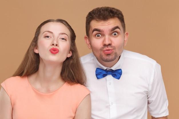 Jeune couple regardant la caméra avec une grimace et s'embrassant avec amour