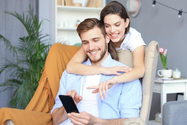 Jeune couple regardant du contenu en ligne dans un téléphone intelligent assis sur une chaise à la maison dans le salon.